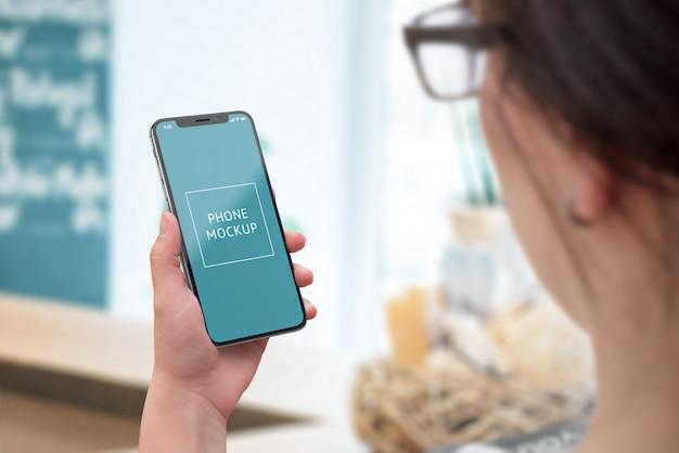 Maquete de telefone na mão da mulher. vista por cima do ombro. telefone inteligente moderno com bordas finas Psd Premium