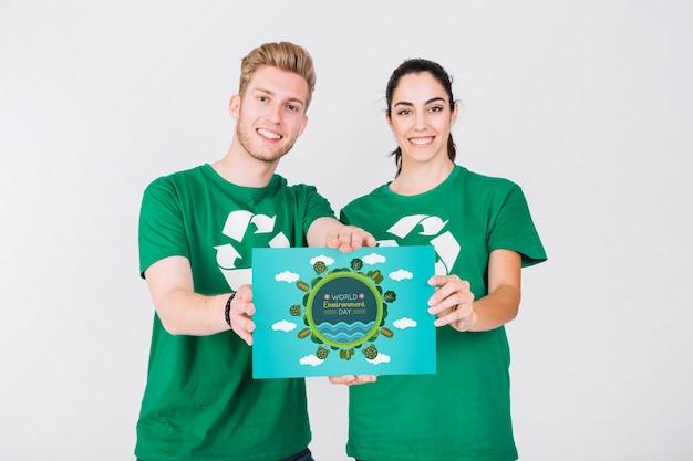 Maquete do dia do meio ambiente com papel de exploração de casal voluntário Psd grátis