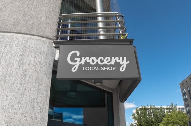 Maquete do logotipo branco na cinza sinalização retangular pendurado na fachada do edifício Psd Premium