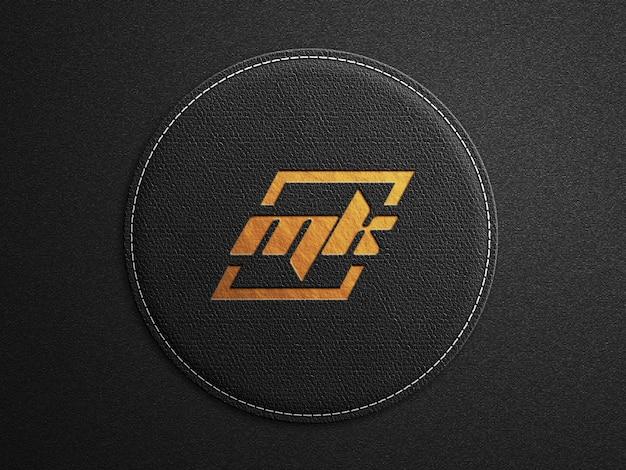 Maquete do logotipo na superfície arredondada de couro preto com estampa dourada em relevo Psd Premium