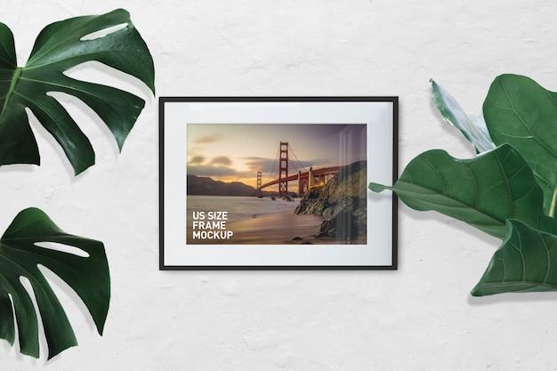 Maquete do quadro de foto paisagem preto na parede branca com plantas Psd Premium