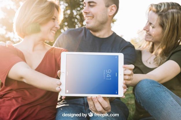 Maquete do tablet com amigos ao ar livre Psd grátis