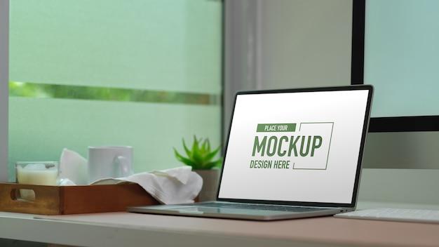 Maquete laptop na mesa do computador com caneca e vela na bandeja de madeira Psd Premium