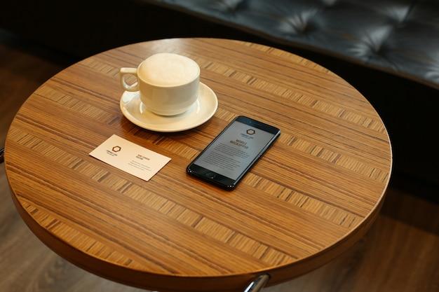 Maquetes de smartphone e cartão de visita psd na mesa-redonda na caffee Psd Premium