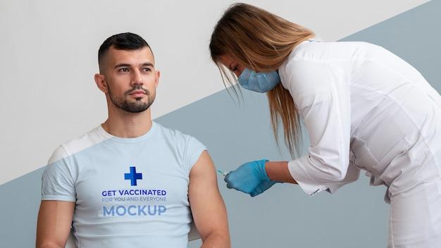 Médica vacinando um homem Psd grátis