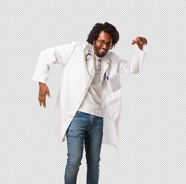 Médico americano africano bonito ouvindo música, dançando e se divertindo, movendo-se, gritando e expressando felicidade, liberdade Psd Premium