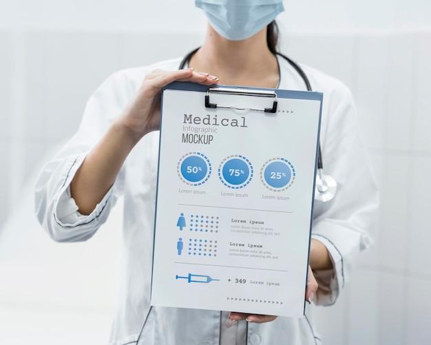 Médico com máscara segurando uma maquete de prancheta Psd grátis