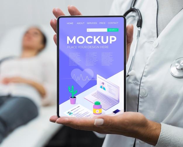 Médico segurando a maquete do tablet perto do paciente Psd grátis