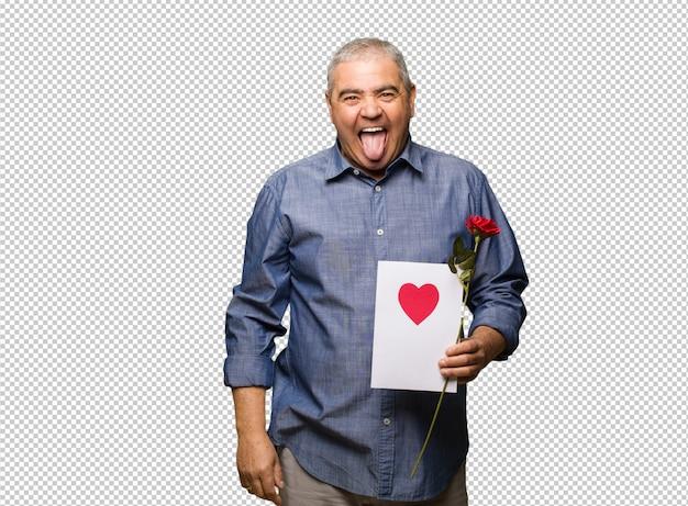 Meio envelhecido homem comemorando dia dos namorados funnny e amigável mostrando a língua Psd Premium