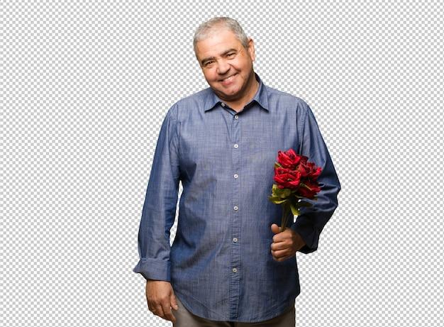 Meio envelhecido homem comemorando o dia dos namorados alegre com um grande sorriso Psd Premium
