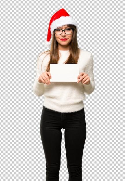 Menina com comemorando as férias de natal, segurando um cartaz branco vazio para inserir um conceito Psd Premium
