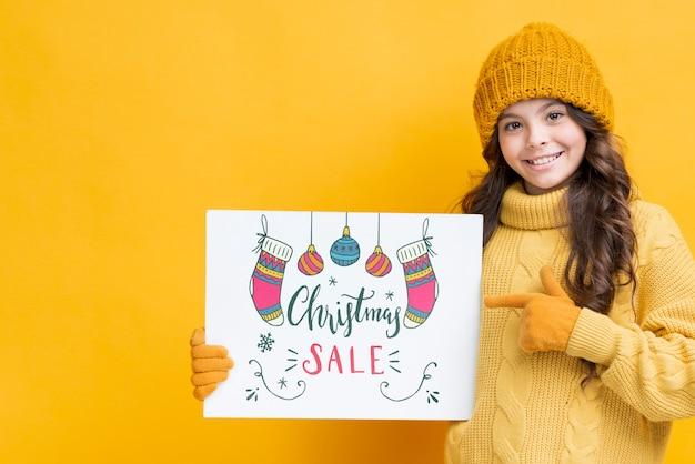 Menina com folha de papel para vendas de natal Psd grátis
