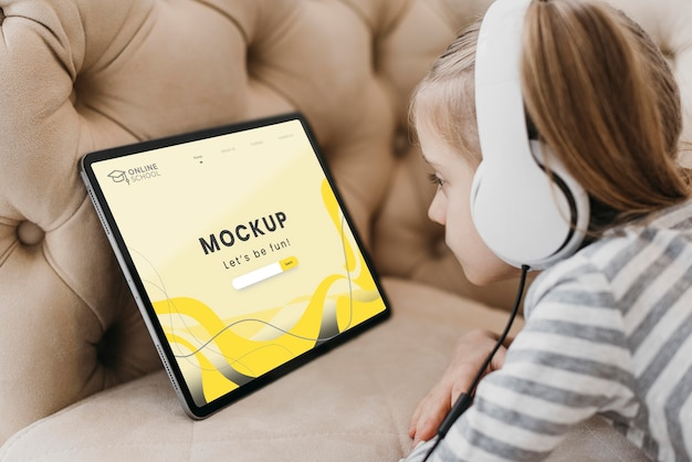 Menina com tablet no sofá Psd Premium