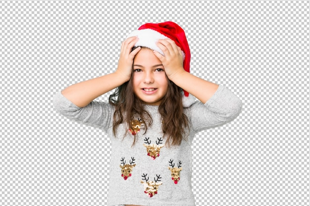 Menina comemorando o dia de natal ri alegremente, mantendo as mãos na cabeça. conceito de felicidade. Psd Premium