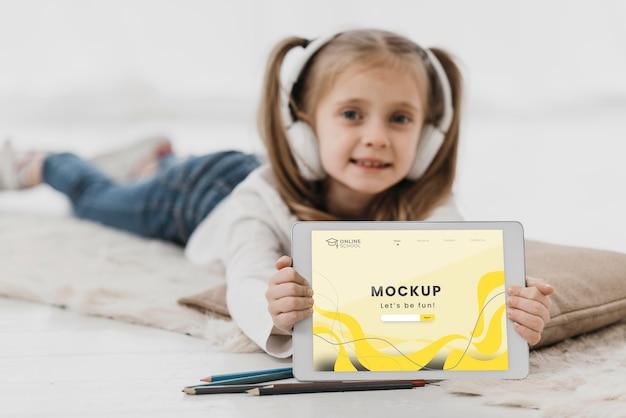 Menina na cama com tablet Psd grátis