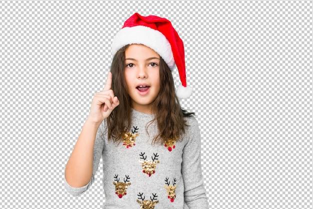 Menina que comemora o dia de natal que tem uma ideia, conceito da inspiração. Psd Premium