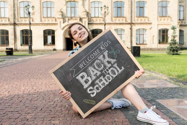 Menina, segurando, costas, para, escola, quadro-negro, mock-up Psd grátis