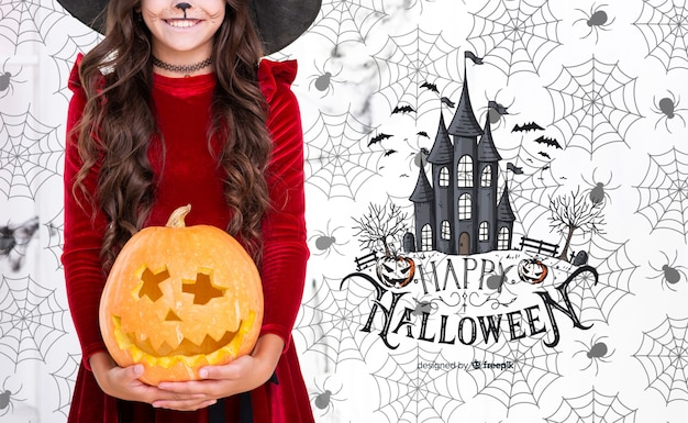 Menina segurando uma abóbora esculpida para festa de halloween Psd grátis