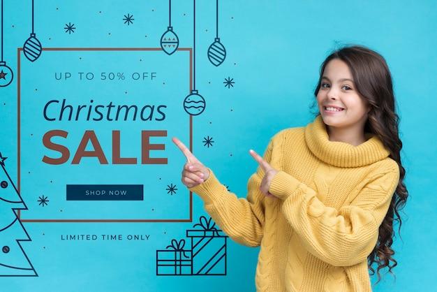 Menina sorridente, apontando para a mensagem com promoções no natal Psd grátis
