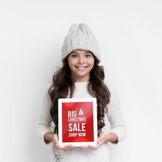 Menina sorridente com folha de papel para vendas de inverno Psd grátis