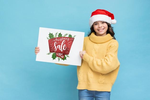 Menina sorridente, segurando a folha de papel com mensagem de vendas Psd grátis