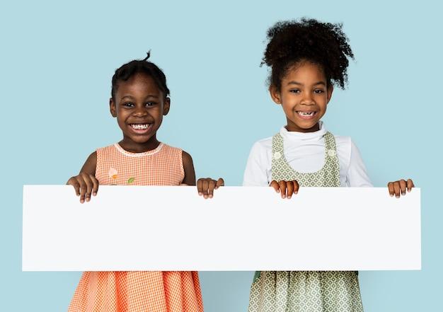 Menina, sorrindo e segurando o cartaz de pesquisa em branco Psd grátis