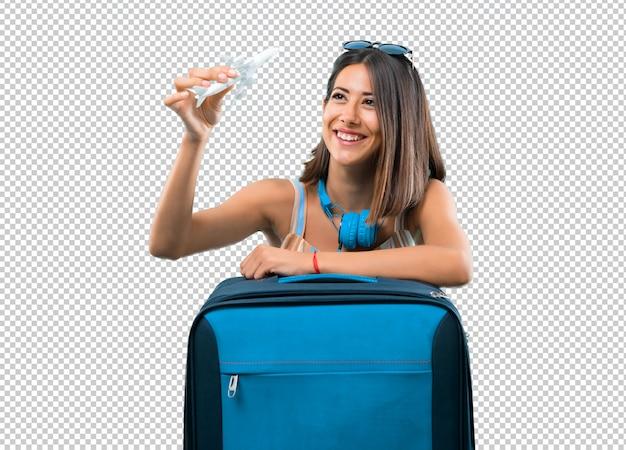 Menina viajando com sua mala e segurando um avião de brinquedo Psd Premium