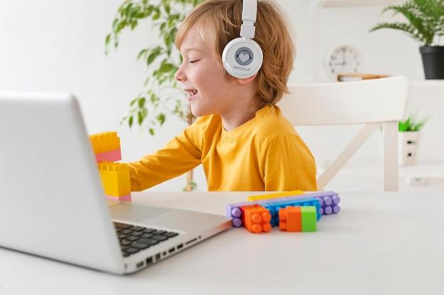 Menino com fones de ouvido usando laptop Psd grátis