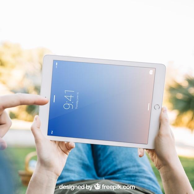Mentindo homem segurando tablet maquete Psd grátis