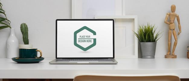 Mesa de escritório em casa com maquete de laptop, xícara de café e decorações Psd Premium