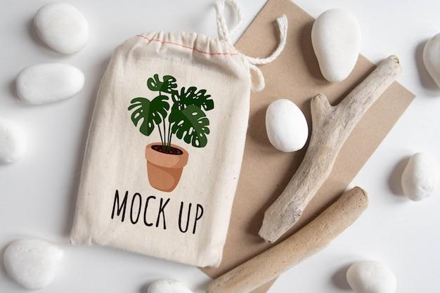 Mock-se de saco de algodão de baralho de tarô com envelope de textura papel artesanal marrom e vara rústica na mesa branca Psd Premium