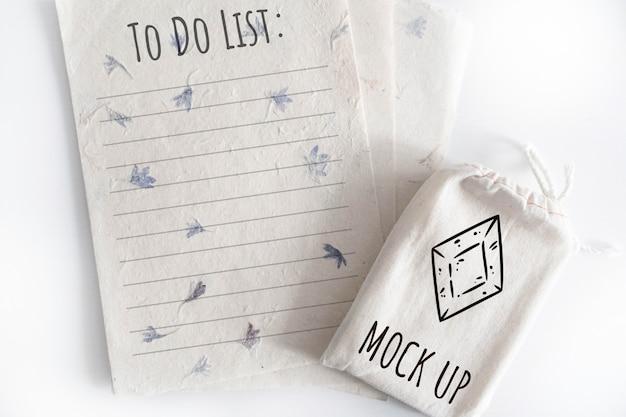 Mock-se do saco de algodão de baralho de tarô com folhas de papel de textura no fundo branco Psd Premium