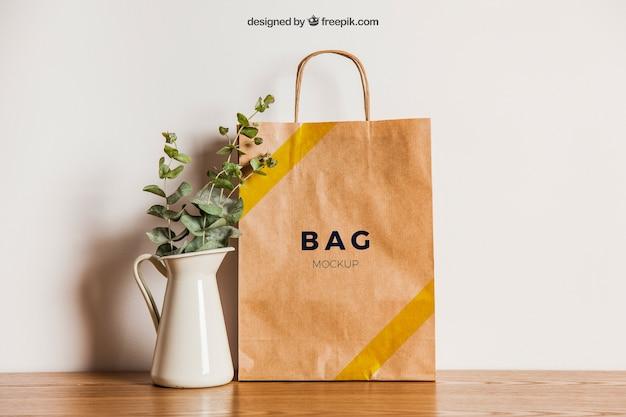 Mockup de saco de papel ao lado do vaso de flores Psd Premium