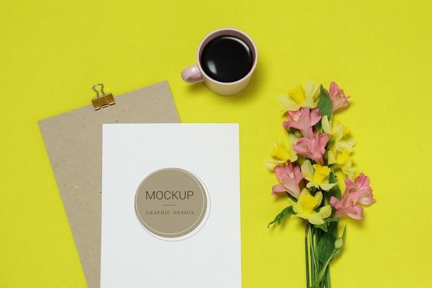 Moldura de papel de maquete sobre o fundo amarelo com flores, xícara de café Psd Premium
