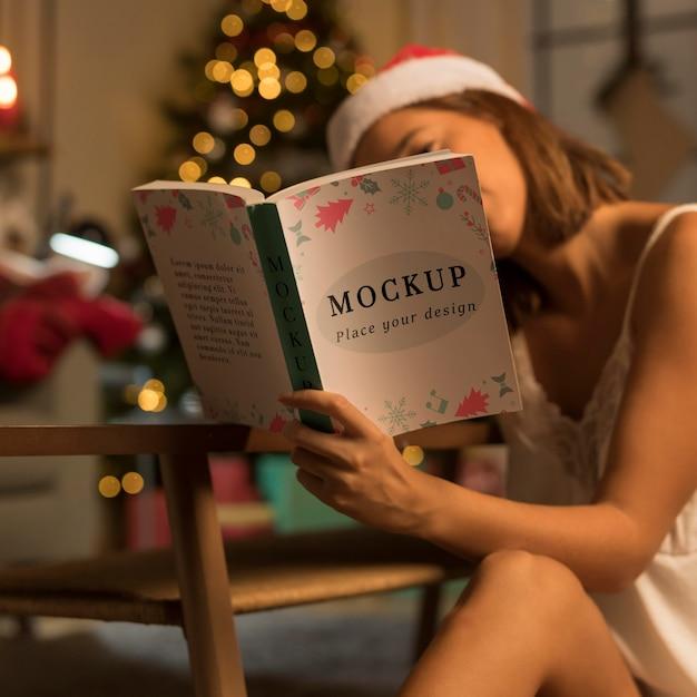 Mulher adulta lendo um livro de natal com maquete Psd Premium