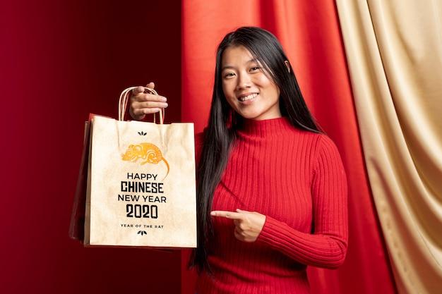 Mulher apontando para bolsa com mensagem de feliz ano novo Psd grátis