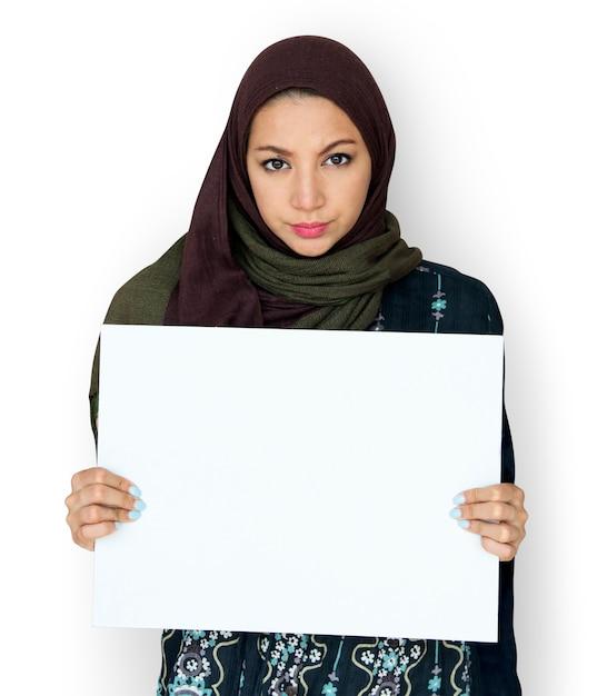 Mulher árabe segurando a placa de papel em branco Psd grátis