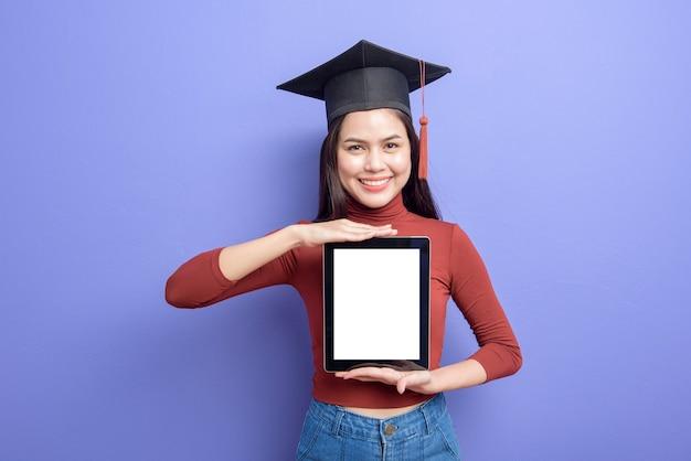 Mulher bonita no chapéu de formatura está segurando a maquete do tablet Psd Premium