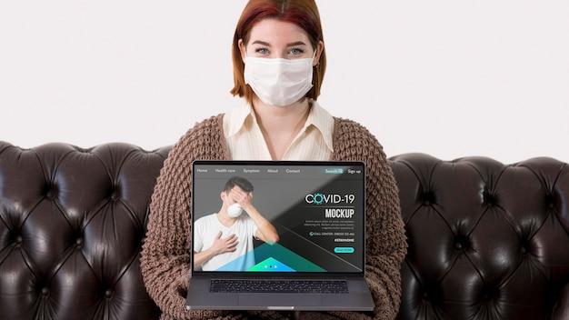 Mulher com máscaras segurando laptop enquanto está sentada no sofá Psd grátis