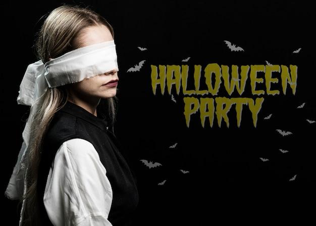 Mulher com os olhos amarrados com uma fantasia de halloween de pano branco Psd grátis