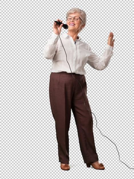 Mulher de corpo inteiro sênior feliz e motivada, cantando uma música com um microfone, apresentando um evento ou ter uma festa, aproveite o momento Psd Premium