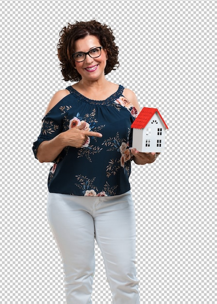 Mulher de meia idade feliz e confiante, mostrando um modelo de casa em miniatura, tentando vendê-lo, casa e família Psd Premium