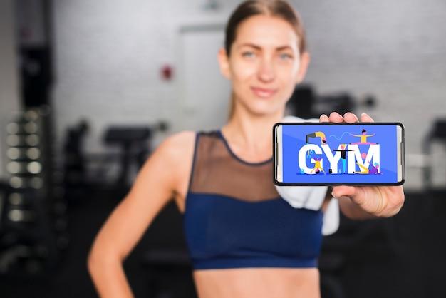 Mulher desportiva feliz apresentando maquete de smartphone Psd grátis