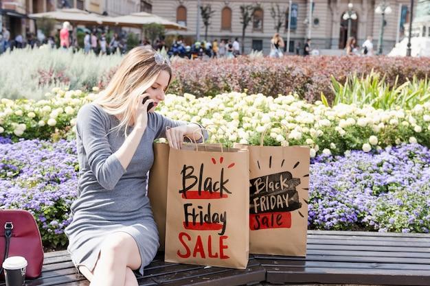 Mulher, em, cidade, com, pretas, sexta feira, sacolas Psd grátis