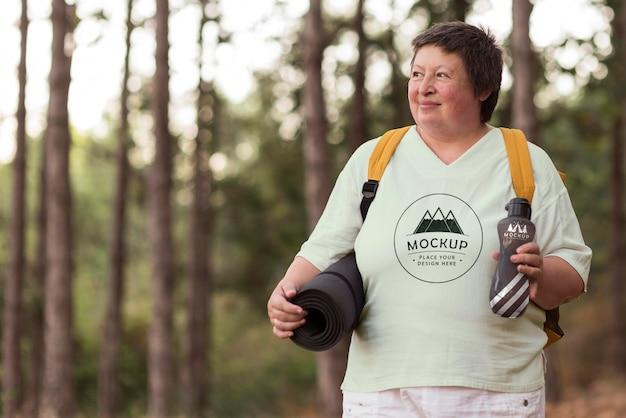 Mulher idosa acampando com um mock-up de camiseta Psd grátis