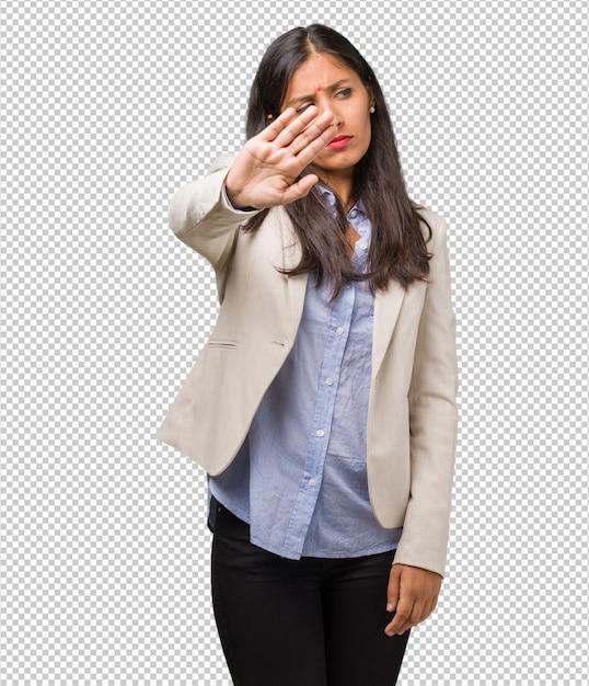 Mulher indiana de negócios jovem séria e determinada, colocando a mão na frente, gesto de parada, negar o conceito Psd Premium