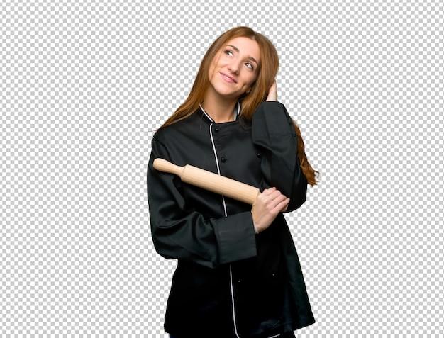 Mulher jovem chef ruiva pensando uma idéia enquanto coçando a cabeça Psd Premium