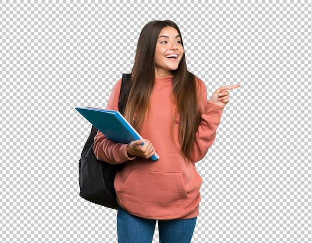 Mulher jovem, estudante, segurando, cadernos, apontar dedo, ao lado Psd Premium