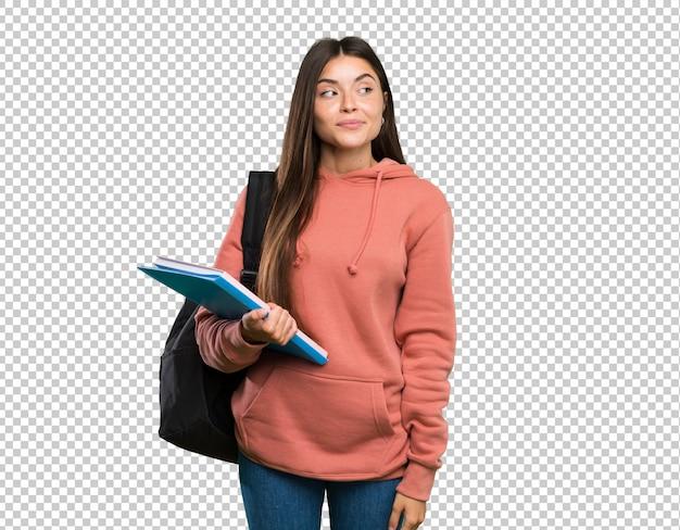 Mulher jovem, estudante, segurando, cadernos, fazendo, dúvidas, gesto, olhar, lado Psd Premium