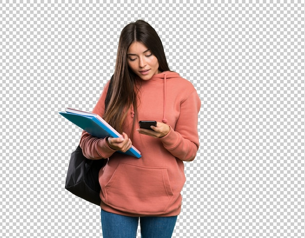 Mulher jovem estudante segurando os cadernos enviando uma mensagem com o celular Psd Premium